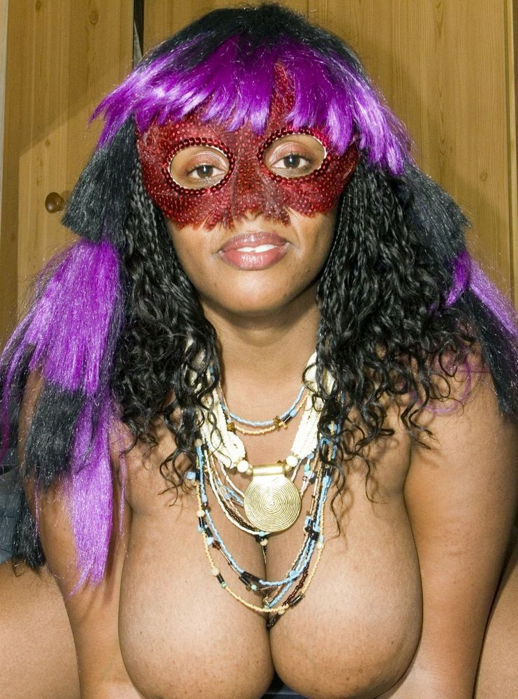 Lush dark-hued female in carnival mask..